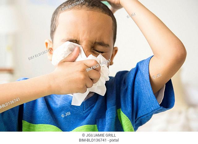 Mixed race boy blowing his nose