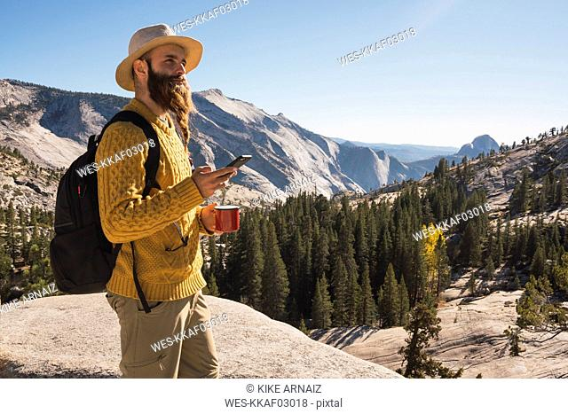 USA, California, Yosemite National Park, hiker using smartphone and holding cup