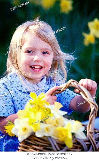 little girl carrying a basket of daffodils