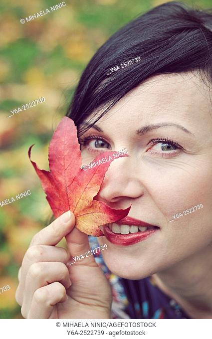 Smiling mid adult woman holding leaf close to her face, autumn