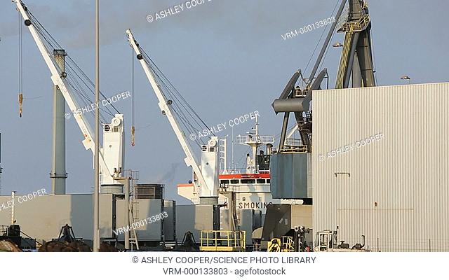 Cranes loading boats at Ijmuiden, Amsterdam, Netherlands with emissions from the Tata steel works