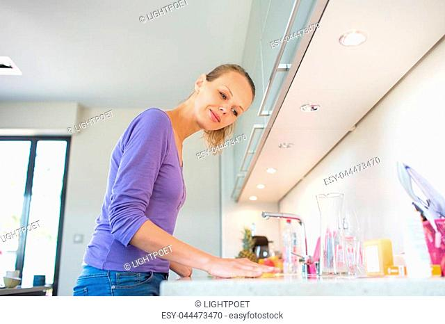 Pretty, young woman cleaning her modern kitchen after cooking lunch (shallow DOF; color toned image)