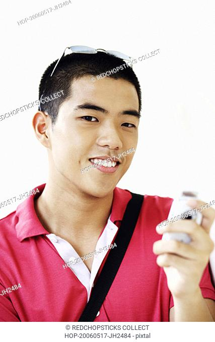 Portrait of a young man operating a mobile phone