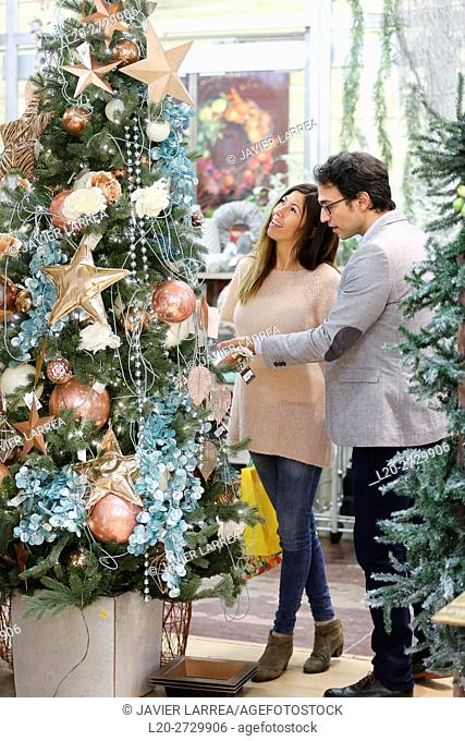 Couple buying Christmas ornaments in garden center