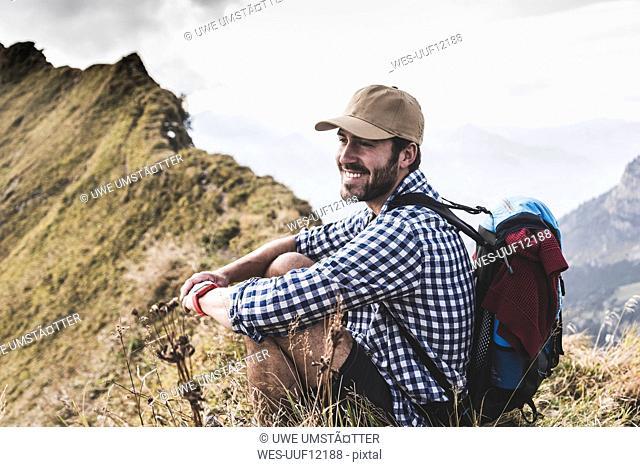Germany, Bavaria, Oberstdorf, smiling hiker resting on mountain ridge