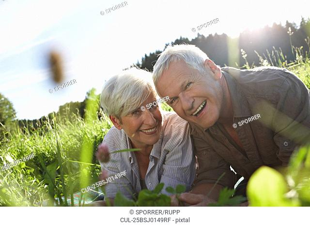 Senior couple lying in meadows smiling