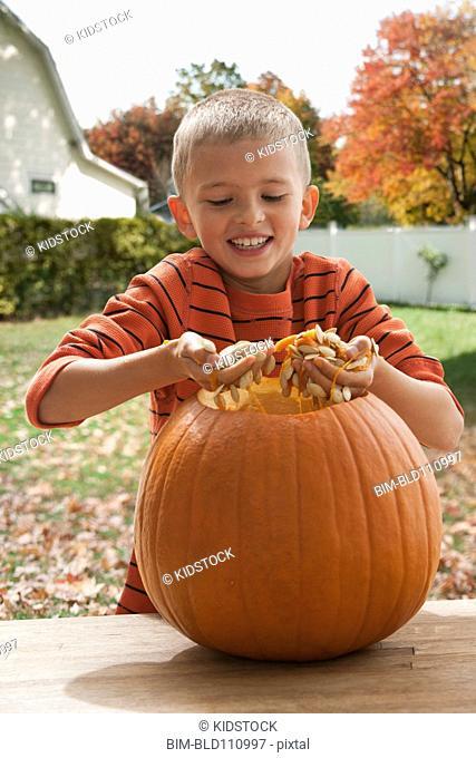 Boy carving pumpkin outdoors