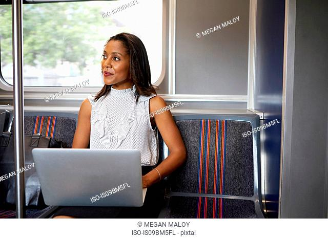 Businesswoman using laptop on train