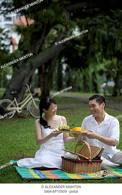 Singapore, Man and woman sitting on picnic blanket in park