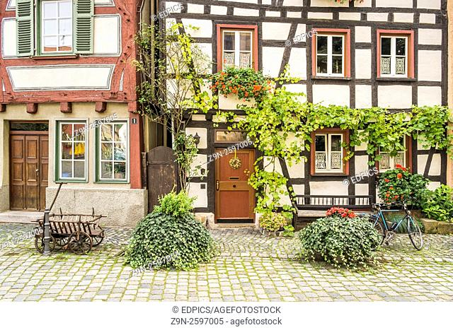 bicycle and historic hand waggon in front of the flowerdecked facade of half timbered houses in the historic part of esslingen, baden-wuerttemberg, germany