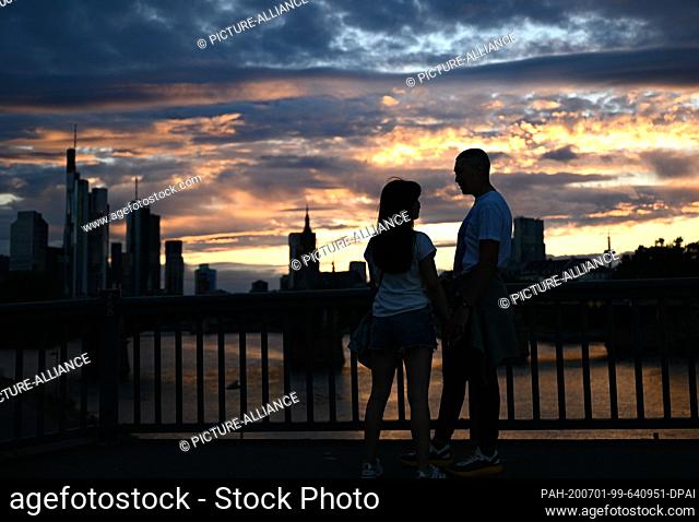 01 July 2020, Hessen, Frankfurt/Main: A couple watches the sunset on the raft bridge in the evening. Photo: Arne Dedert/dpa