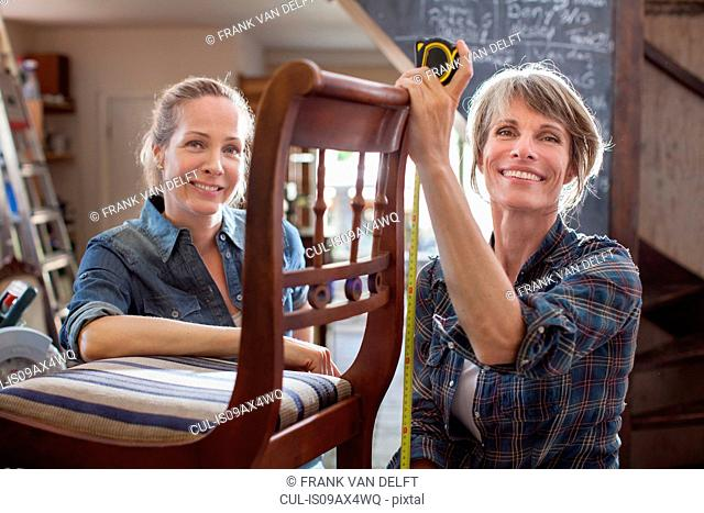 Woman in workshop with chair looking at camera smiling