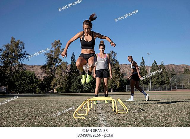 Woman jumping over agility hurdles