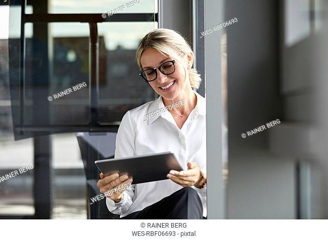 Serene businesswoman sitting on ground in office, using digital tablet