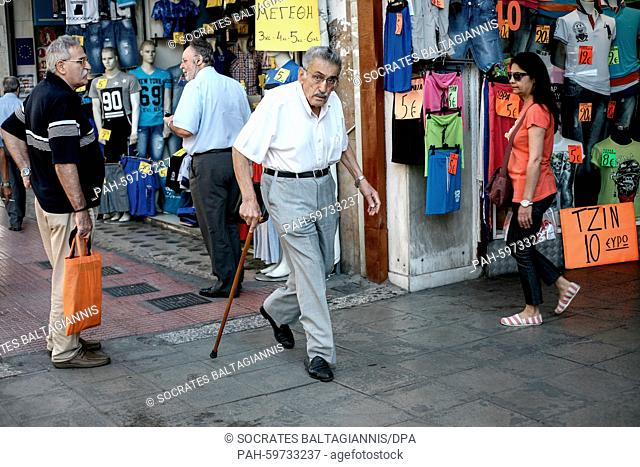 An elderly man walks next to a clothes shop near Omonia square in Athens, Greece on the 2nd of July 2015. Greece's government has made new concessions in talks...