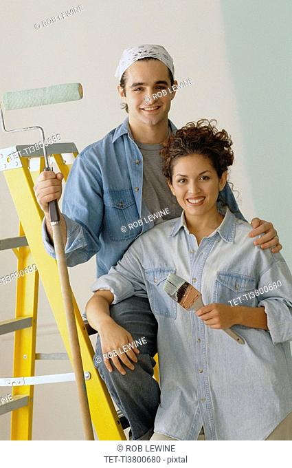 Happy couple painting the walls in their home