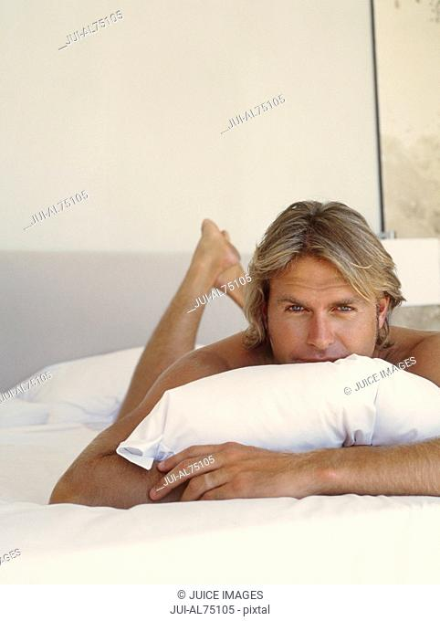 Portrait of a young man lying on a bed