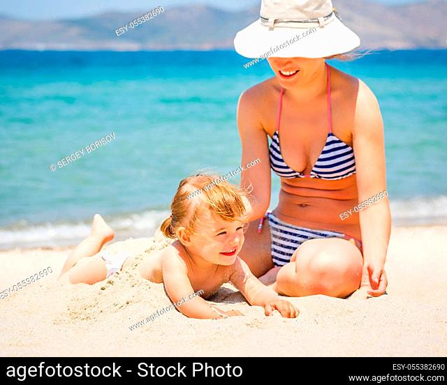 Mother with little daughter playing on the beach