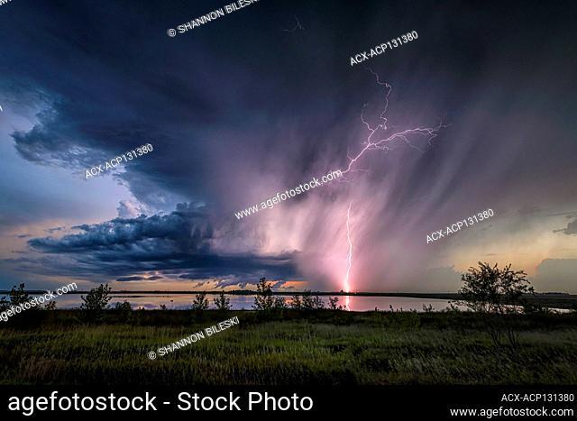 Storm with lightning reflecting off lake in rural North Dakota United States