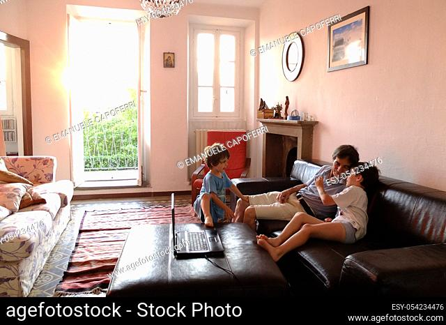 Children play with his grandfather at home on the couch