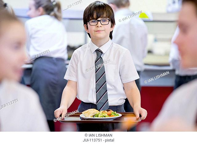 Portrait smiling middle school student carrying lunch tray in school cafeteria
