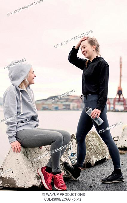 Two female running friends chatting on dockside