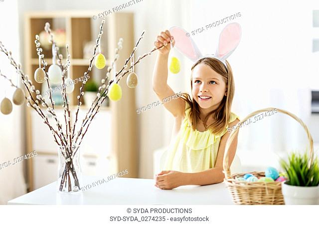 girl decorating willow by easter eggs at home