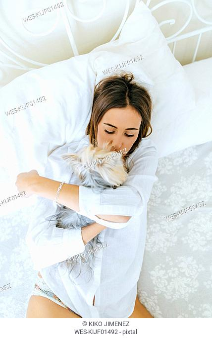 Woman lying on bed with hugging and kissing her Yorkshire Terrier, top view