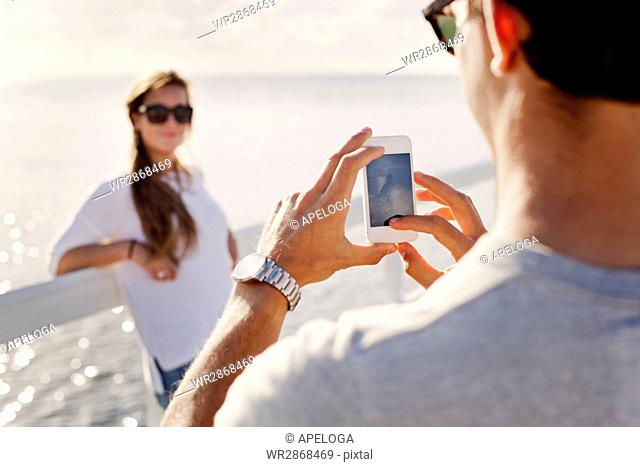 Young man photographing girlfriend on pier over sea