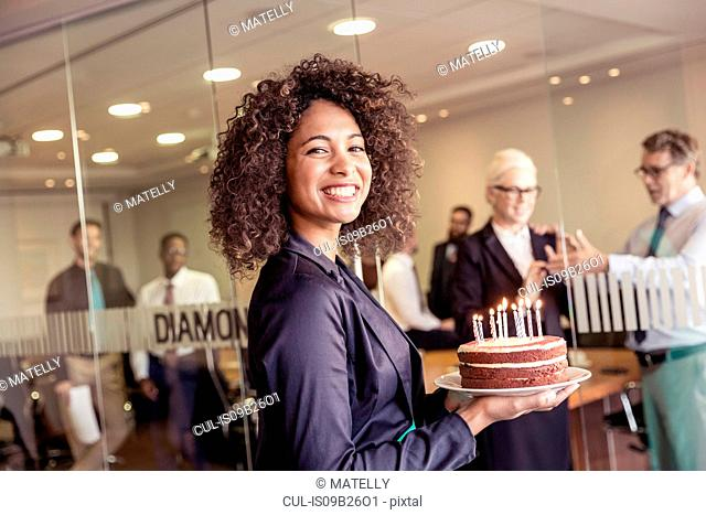 Young woman presenting cake with candles to business team in boardroom