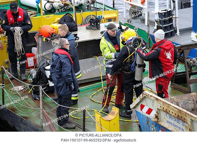 07 January 2019, Hamburg: A diver of the explosive ordnance clearance service as well as other fire brigade and police personnel are working at the site where...