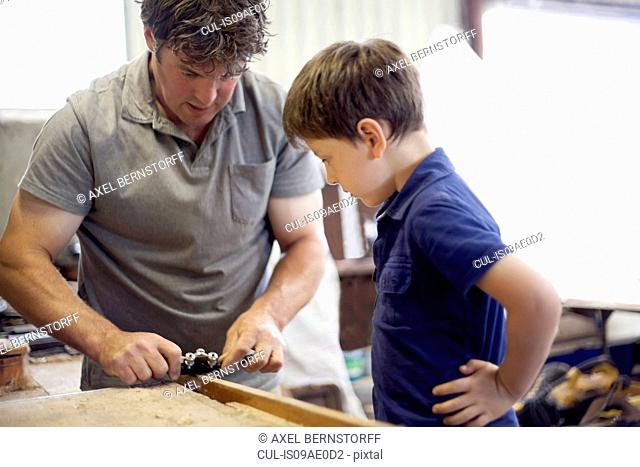 Father showing son carpentry in boat workshop
