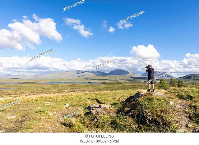 Great Britain, Scotland, Scottish Highlands, Glencoe, Rannoch Moor, Tourist photographing Loch Beinn Chaorach and Loch Ba