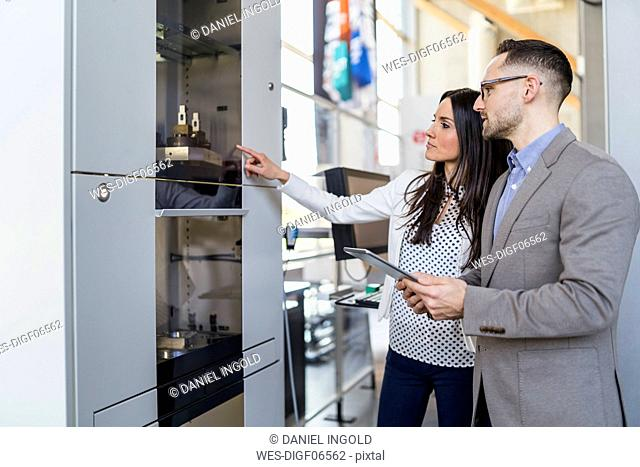 Businessman and businesswoman talking at a machine in modern factory