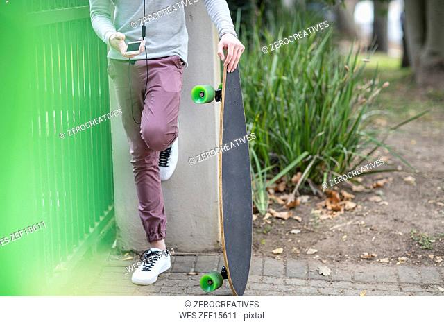 Close-up of boy holding skateboard and using cell phone