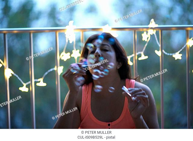 Mature woman blowing bubbles by illuminated decorative lights at dusk