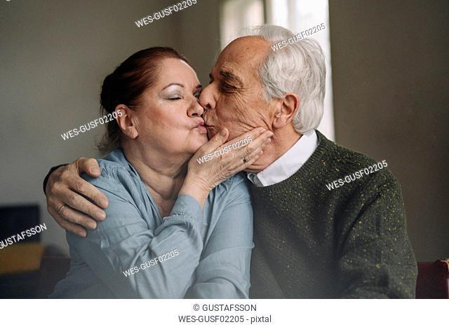 Senior couple kissing at home