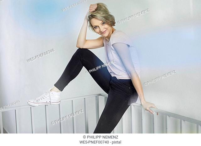 Portrait of smiling blond woman sitting on railing