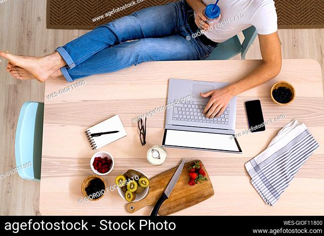 Man holding smoothie jar while using laptop sitting at table in kitchen
