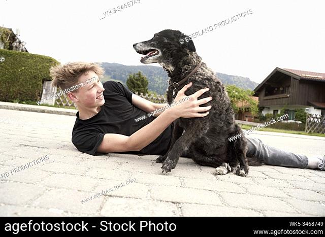 Teenager playing with his dog, in Gaissach, Bavaria, Germany