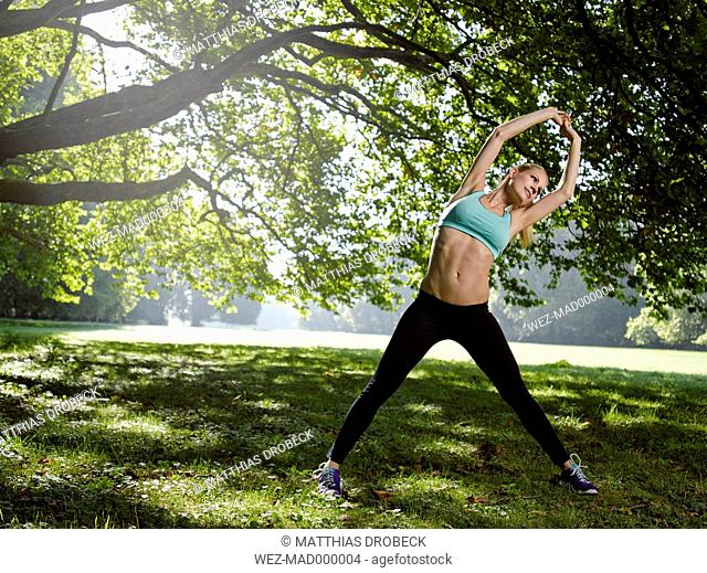 Germany, Young athletic woman doing sports, stretching exercise