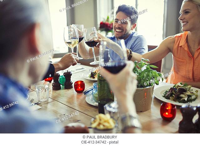 Smiling friends celebrating, toasting wine glasses at restaurant table