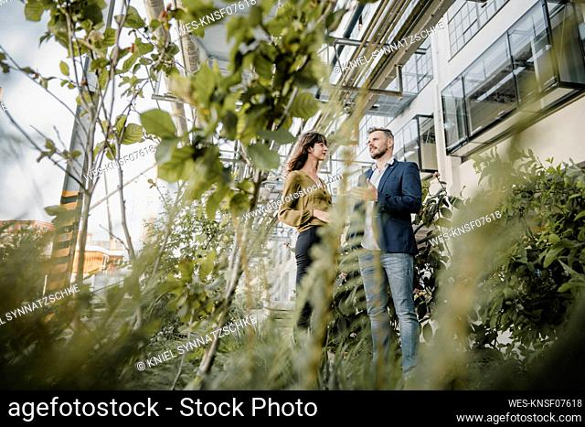 Businessman and casual businesswoman talking outdoors