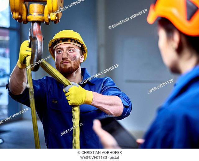 Industrial worker fixing hoist sling on indoor crane, female colleague controlling with digital tablet