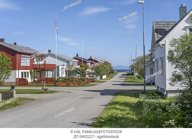 cityscape with street to sea side flanked by spaced-out traditional houses at artic touristic village, shot under bright summer light at Andenes, Andoya