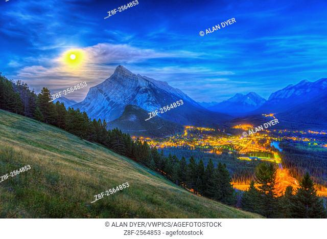 The supermoon of August 10, 2014 rising behind Mt. Rundle and Banff townsite, as shot from the Mt. Norquay viewpoint looking south over the valley