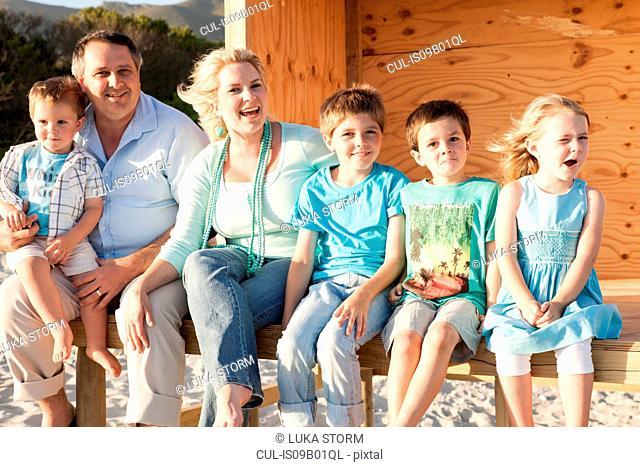 Family at beach looking at camera smiling