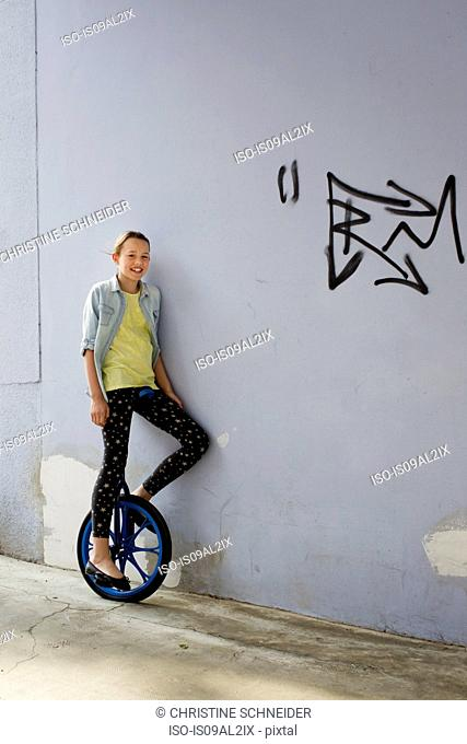 Teenage girl on unicycle, portrait