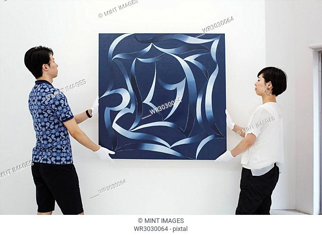 Man in blue shirt and woman wearing white shirt hanging modern painting on white wall in art gallery