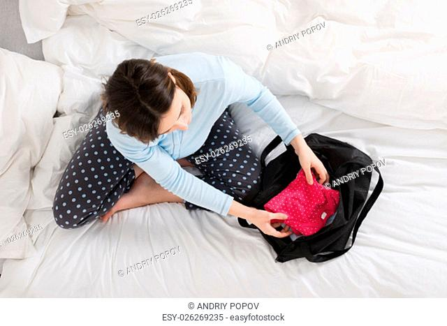 Young Pregnant Woman Sitting On Bed Packing Baby Clothes Into Bag